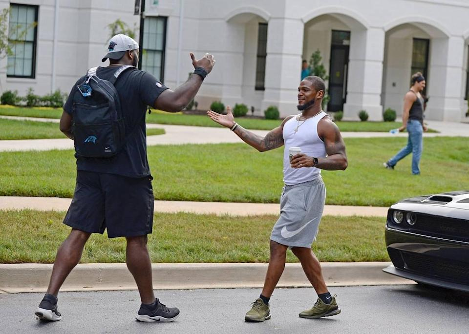 Carolina Panthers tackle Taylor Moton, left and linebacker Denzel Perryman, right, greet one another after arriving at their dormitory on the campus of Wofford College in Spartanburg, SC on Tuesday, July 27, 2021. The Panthers will hold their first training camp practice on Wednesday, July 28, 2021.