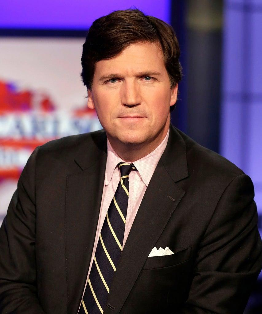 """Mandatory Credit: Photo by AP/Shutterstock (8467748e) Tucker Carlson, host of """"Tucker Carlson Tonight,"""" poses for photos in a Fox News Channel studio, in New York Tucker Carlson, New York, USA – 02 Mar 2017"""