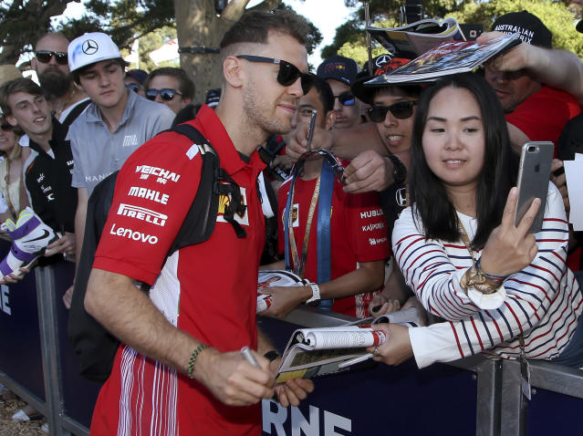 Ferrari driver Sebastian Vettel, center, of Germany meets fans as he arrives at the track at the Australian Formula One Grand Prix in Melbourne, Friday, March 23, 2018. The first race of the 2018 seasons is on Sunday. (AP Photo/Rick Rycroft)