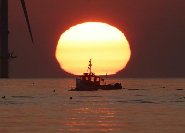 A fishing boat sails in front of the rising sun near Blyth pier in Northumberland