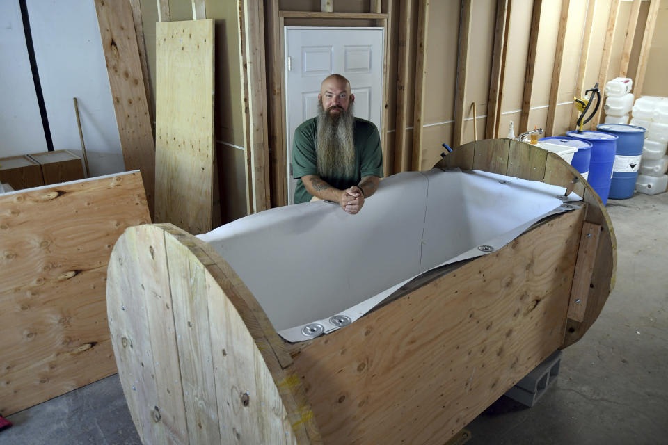 In this Wednesday, Aug. 11, 2021, photo, Seth Viddal, who co-owns The Natural Funeral, stands behind a nearly completed human body composting vessel in Arvada, Colo. On Sept. 7, Colorado became the second state after Washington to allow human body composting, and Oregon will allow the practice beginning next July. The vessel will be packed with wood chips and straw and will be able to compost a body in six months. About the size of a standard grave, the rectangular insulated wooden box is lined with waterproof roofing material and packed with wood chips and straw. Two large spool wheels on either end allow it to be rolled across the floor, providing the oxygenation, agitation and absorption required for a body to compost. (AP Photo/Thomas Peipert)