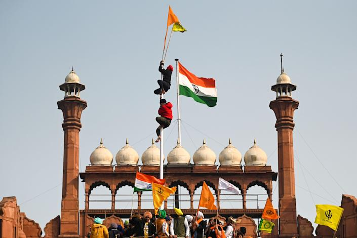 <p>Protesters climb a flagpole at the ramparts of the Red Fort as farmers continue to demonstrate against the central government's recent agricultural reforms in Delhi</p> (AFP)