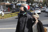 People wearing masks to help protect against the spread of coronavirus, walk before a nationwide lockdown, in Ankara, Turkey, Wednesday, April 21, 2021. Turkey continued to post record-high daily COVID-19 deaths on Wednesday, with 362 fatalities registered in the last 24 hours, Health Ministry data showed. The country, which now ranks among the worst-hit nations, also reported 61,967 new confirmed cases.(AP Photo/Burhan Ozbilici)