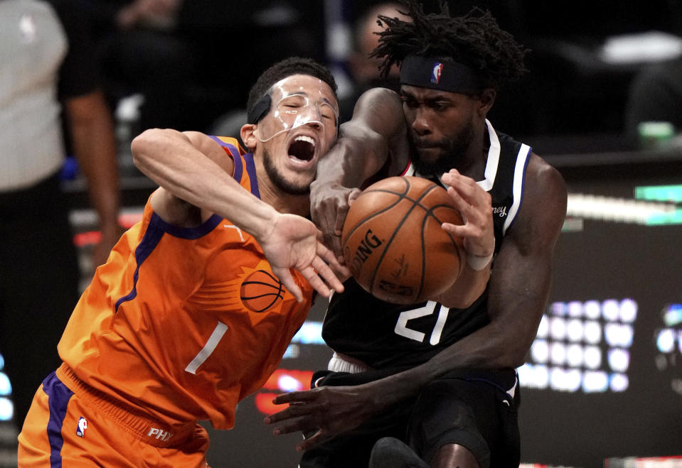 Patrick Beverley #21 of the LA Clippers blocks the shot by Devin Booker #1 of the Phoenix Suns in the first half of game three of a Western Conference finals NBA playoff basketball game at the Staples Center in Los Angeles on Thursday, June 24, 2021. (Keith Birmingham/The Orange County Register via AP)