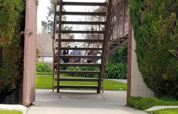 In this still image taken from video, investigators are seen at the apartment building where authorities say a mother threw her young son from a second-story apartment landing and jumped herself as police arrived in Upland, Calif., Tuesday, Feb. 26, 2019. The mother and 1-year-old boy were hospitalized in stable condition, police said. A baby girl was found inside the apartment not breathing and though her breathing was restored, she died at the hospital. (Beatriz Valenzuela/The Orange County Register/SCNG via AP)