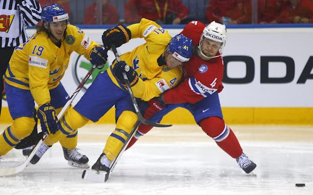 Norway's Daniel Sorvik, right, and Sweden's Calle Jarnkrok, left, and Gustav Nyquist battle for the puck during the Group A preliminary round match at the Ice Hockey World Championship in Minsk, Belarus, Tuesday, May 13, 2014. (AP Photo/Sergei Grits)