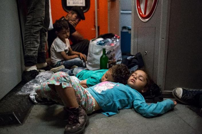 Migrant children sleep on the floor on the train from Budapest to Munich at the Austrian - Hungarian border in Hegyeshalom on August 31, 2015 (AFP Photo/Vladimir Simicek)