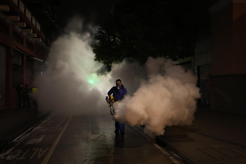 A worker in personal protective equipment sanitizes a street in downtown Guatemala City, Thursday, July 1, 2021, in the wake of a spike in the number of coronavirus cases. Daily infections of COVID-19 number in the hundreds while less than one percent of the population has been fully immunized, according to government data. (AP Photo/Moises Castillo)