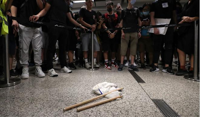 Protesters with sticks they found that were carried by a man they apprehended at Hong Kong International Airport. Photo: Sam Tsang