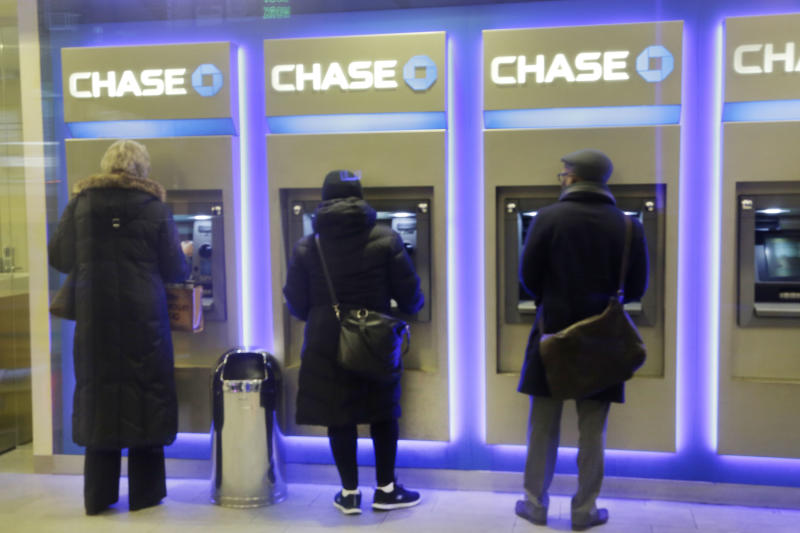 Customers uses ATM's at at a branch of Chase Bank, Wednesday, Jan. 14, 2015 in New York. JPMorgan Chase reported a 7 percent drop in fourth-quarter earnings Wednesday, hit by more legal costs and a drop in trading revenue. JPMorgan, the biggest U.S. bank by assets, said it earned $4.93 billion, or $1.19 a share, for the three-month period ending in December. (AP Photo/Mark Lennihan)