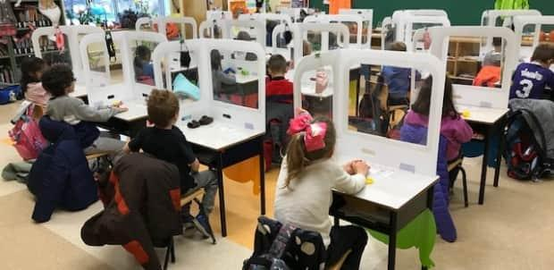 Children in Grade 1 at Steve MacLean Public School in Ottawa sit behind protective barriers in the classroom. Teachers are worried as variant cases rise in the city. (Submitted by Lisa Levitan - image credit)