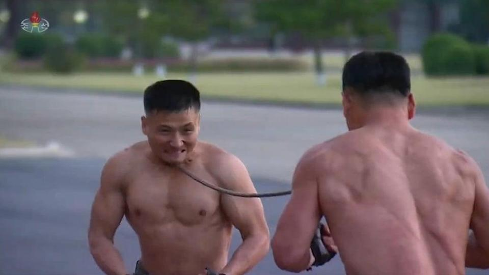 Screen grab from the video shows two soldiers bending an iron rod with their necks (KCTV)