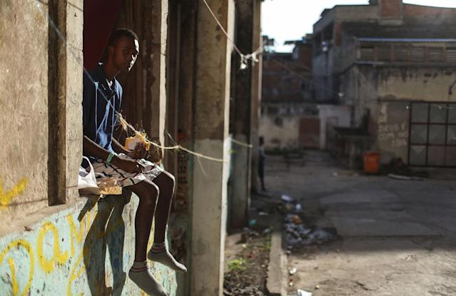 <p>A man named Jefferson eats lunch as he sits in the window at his family's home in the Mangueira favela, May 4, 2017, in Rio de Janeiro. (Photo: Mario Tama/Getty Images) </p>