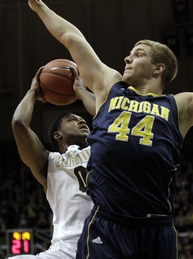 Purdue guard Terone Johnson, left, shoots around the defense of Michigan forward Max Bielfeldt during the first half of an NCAA college basketball game on Wednesday, March 6, 2013, in West Lafayette, Ind. (AP Photo/AJ Mast)