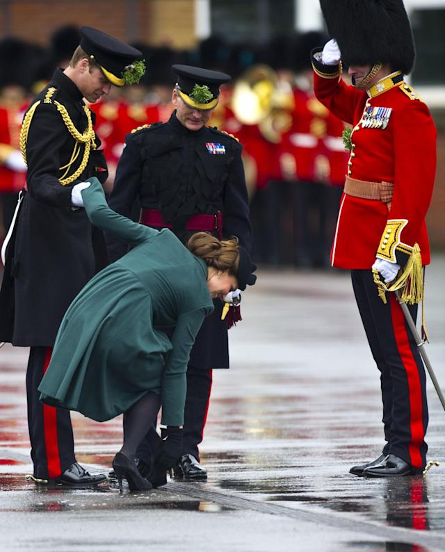 ALDERSHOT, ENGLAND - MARCH 17: Prince William, Duke of Cambridge helps Catherine Duchess of Cambridge as her heel gets stuck in the grating during the Irish Guards' St Patrick's Day Parade at Mons Barracks on March 17, 2013 in Aldershot, England. (Photo by Antony Jones/UK Press via Getty Images)