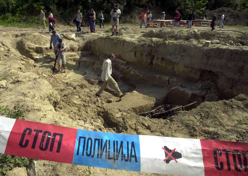 FILE - This is July 9, 2001 file photo of a mass grave which used to contain bodies of Kosovo Albanians at a police compound in Belgrade suburb of Batajnica, Serbia. The banner in front of the hole reads ``Stop Police.'' Amnesty International and regional Balkan human rights organizations, on Wednesday Aug. 29, 2012 urged the Balkan states to investigate the fate of some 14,000 people still missing from the region's conflicts and for those responsible for their disappearance to be punished. The groups charged ahead of the International Day of the Disappeared on Thursday that the Balkan governments lack political will to deal with the problem more than two decades after the wars started. (AP Photo/Darko Vojinovic, File)