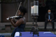 """Violinist Melanie Hill performs during the """"Mourning Into Unity"""" vigil, Monday, Oct. 19, 2020, on a section of 16th Street that has been renamed Black Lives Matter Plaza, near the White House in Washington. Washington's Church of the Epiphany hosted a national candlelight vigil where hundreds of feet of purple fabric symbolizing mourning during COVID-19 was unfurled. (AP Photo/Jacquelyn Martin)"""