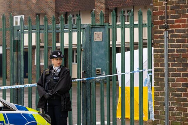 A police officer at the scene of a fatal stabbing at flats on Wisbeach Road in Croydon, London