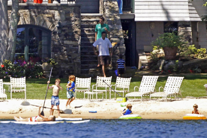Republican presidential candidate Mitt Romney, center, walks with son Josh, rear center, at his vacation home on Lake Winnipesaukee in Wolfeboro, N.H., Sunday, July 1, 2012. (AP Photo/Charles Dharapak)