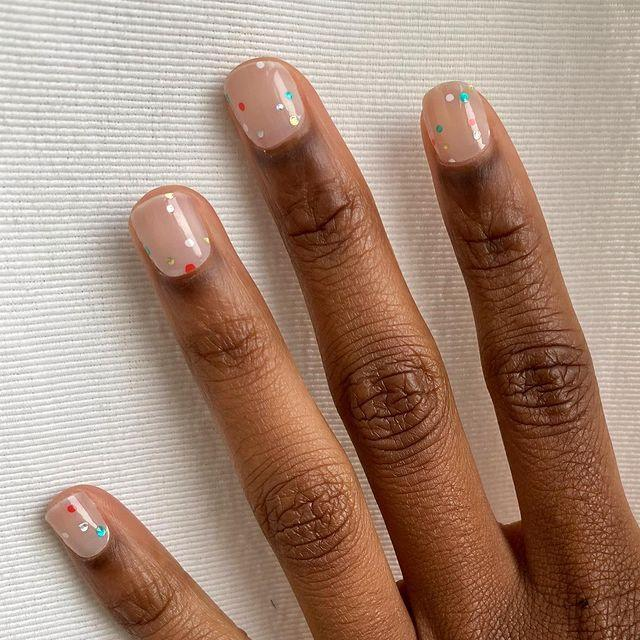 "<p>This cute, confetti-inspired <a href=""https://www.cosmopolitan.com/style-beauty/beauty/g12175665/easy-thanksgiving-nail-art-designs/"" rel=""nofollow noopener"" target=""_blank"" data-ylk=""slk:nail design"" class=""link rapid-noclick-resp"">nail design</a> basically screams ""wear me to all of your fun things in 2021!"". To try the trend, paint your nails in a sheer <a href=""https://www.rootedwoman.com/collections/ethical-non-toxic-nail-polishes/products/vulnerable"" rel=""nofollow noopener"" target=""_blank"" data-ylk=""slk:neutral polish"" class=""link rapid-noclick-resp"">neutral polish</a> and then, using a <a href=""https://www.amazon.com/JSDOIN-Dotting-Tool-Paint-Manicure/dp/B07GBS9WLX/ref=sr_1_5?tag=syn-yahoo-20&ascsubtag=%5Bartid%7C10049.g.34702993%5Bsrc%7Cyahoo-us"" rel=""nofollow noopener"" target=""_blank"" data-ylk=""slk:nail dotting tool"" class=""link rapid-noclick-resp"">nail dotting tool</a>, add confetti-like specks to each nail with silver, green, and <a href=""https://www.cosmopolitan.com/style-beauty/beauty/g8516656/best-red-nail-polish-colors/"" rel=""nofollow noopener"" target=""_blank"" data-ylk=""slk:red nail colors"" class=""link rapid-noclick-resp"">red nail colors</a>.</p><p><a href=""https://www.instagram.com/p/B_nY1DmJ0Ao/?utm_source=ig_embed&utm_campaign=loading"" rel=""nofollow noopener"" target=""_blank"" data-ylk=""slk:See the original post on Instagram"" class=""link rapid-noclick-resp"">See the original post on Instagram</a></p>"