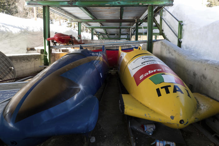 Bobsleds are parked next to the track in Cortina d'Ampezzo, Italy, Wednesday, Feb. 17, 2021. Bobsledding tradition in Cortina goes back nearly a century and locals are hoping that the Eugenio Monti track can be reopened for the 2026 Olympics in the Italian resort. (AP Photo/Gabriele Facciotti)