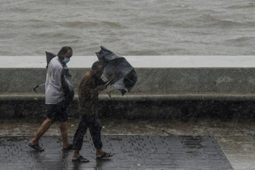 Two men struggle with their umbrellas along Marine Drive in Mumbai as Cyclone Nisarga veered in
