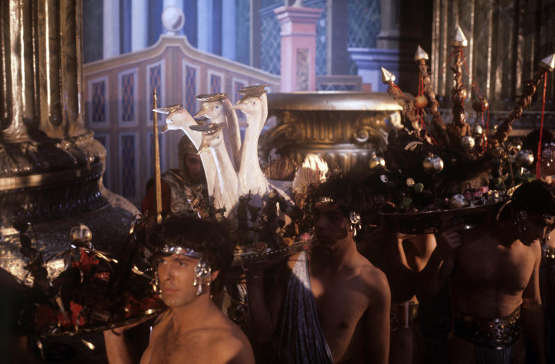 Extras carrying courses on sumptuous trays during a dinner in the film Caligula, My Son. 1979. (Photo by Mondadori via Getty Images)