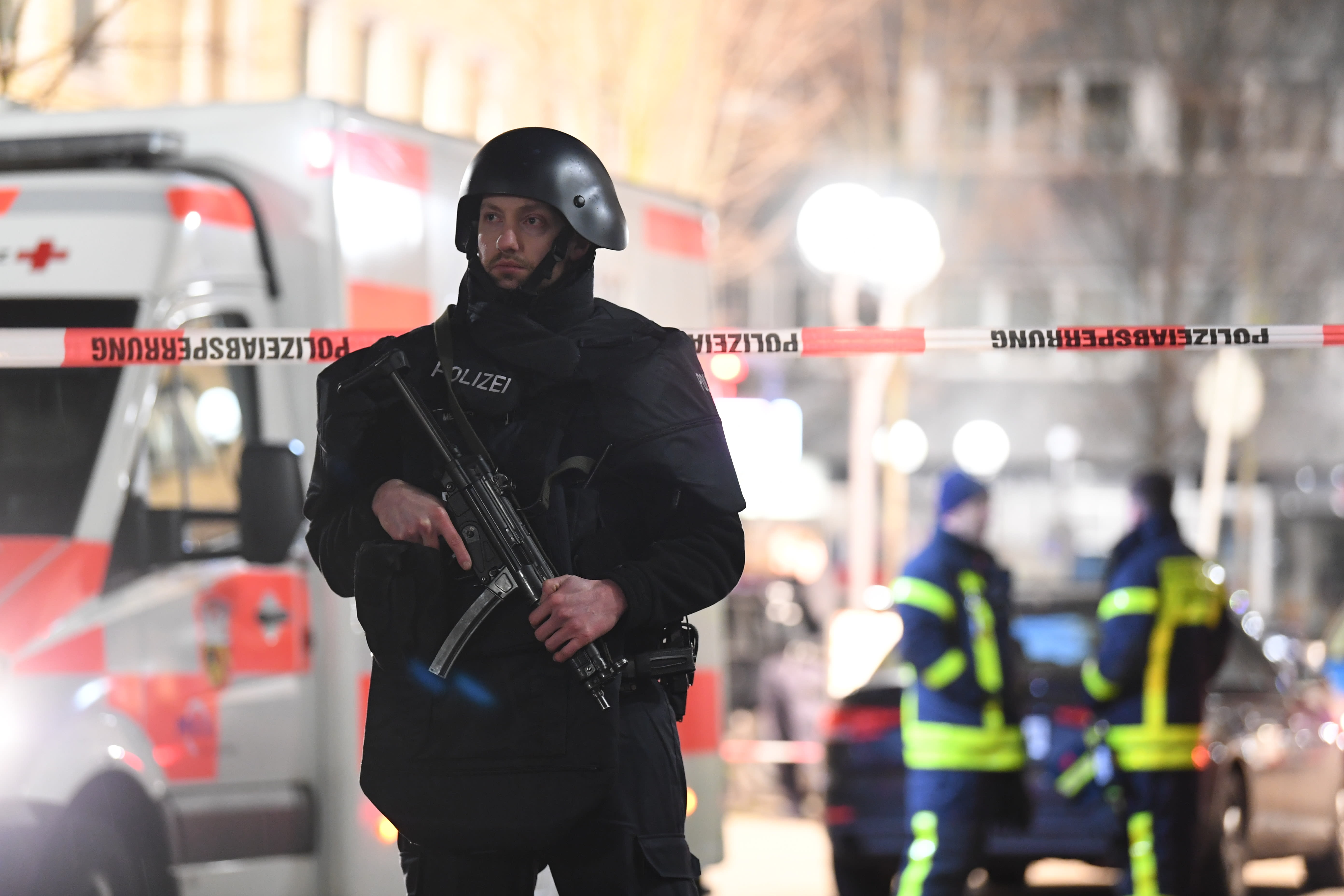A police officer stands guard near the scene in front of a restaurant after a shooting in central Hanau, Germany Thursday, Feb. 20, 2020. Eight people were killed in shootings in the German city of Hanau on Wednesday evening, authorities said. (Boris Roessler/dpa via AP)