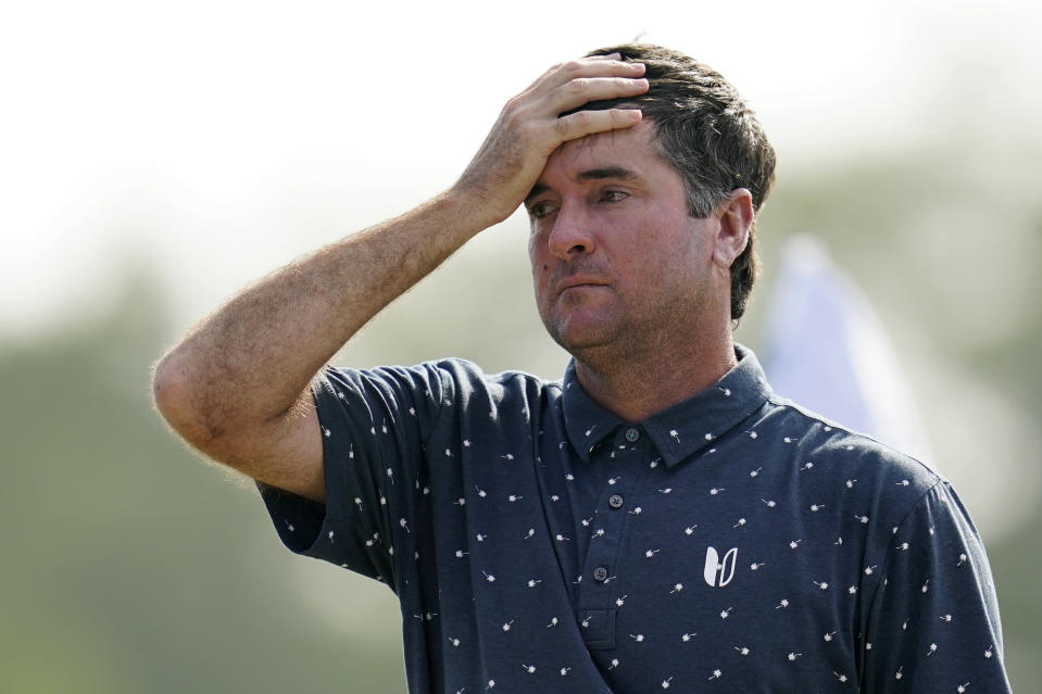 Bubba Watson wipes his head as he walks off the course after making birdie on the 18th hole, to finish the day 17 under with teammate Scottie Scheffler, during the third round of the PGA Zurich Classic golf tournament at TPC Louisiana in Avondale, La., Saturday, April 24, 2021. (AP Photo/Gerald Herbert)
