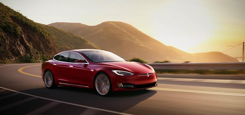 A red Tesla Model S on a mountain road.