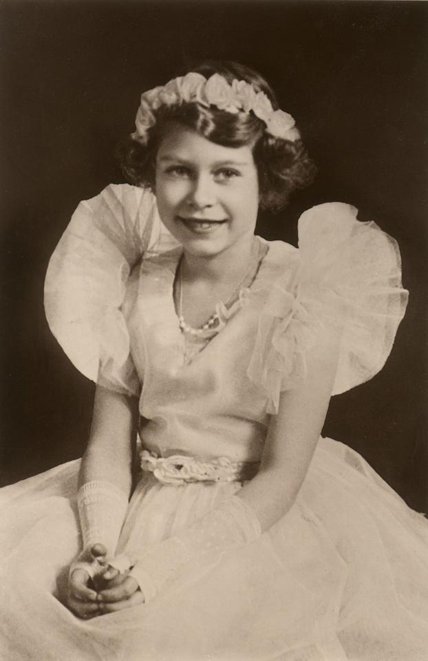 "<p>Looking every bit the princess she was, Elizabeth posed for a portrait at eight years old in a cute tulle-trimmed gown complete with a <a rel=""nofollow"" href=""http://www.goodhousekeeping.com/beauty/hair/g3374/flower-hairstyles-crowns/"">flower crown</a>. She even rocked an '80s trend in those fingerless lace gloves!</p>"