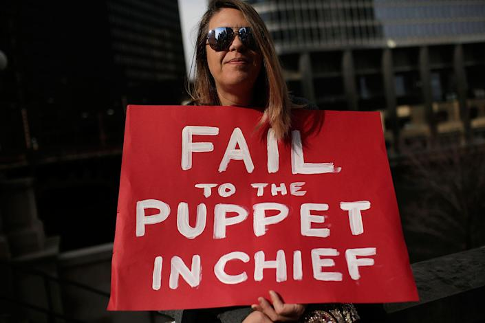 <p>A demonstrator protesting President Trump holds a sign outside Trump International Hotel & Tower during the Presidents' Day holiday, Feb. 20, 2017, in Chicago. (Joshua Lott/AFP/Getty Images) </p>
