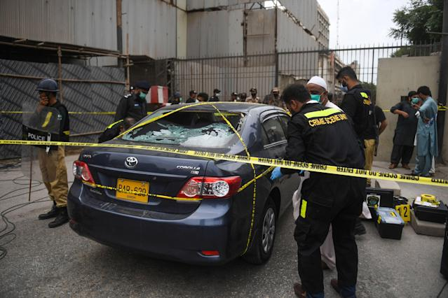 TOPSHOT - Policemen guard as members of Crime Scene Unit investigate around a car used by alleged gunmen at the main entrance of the Pakistan Stock Exchange building in Karachi on June 29, 2020. - Gunmen attacked the Pakistan Stock Exchange in Karachi on June 29, with four of the assailants killed, police said. (Photo by Asif HASSAN / AFP) (Photo by ASIF HASSAN/AFP via Getty Images)