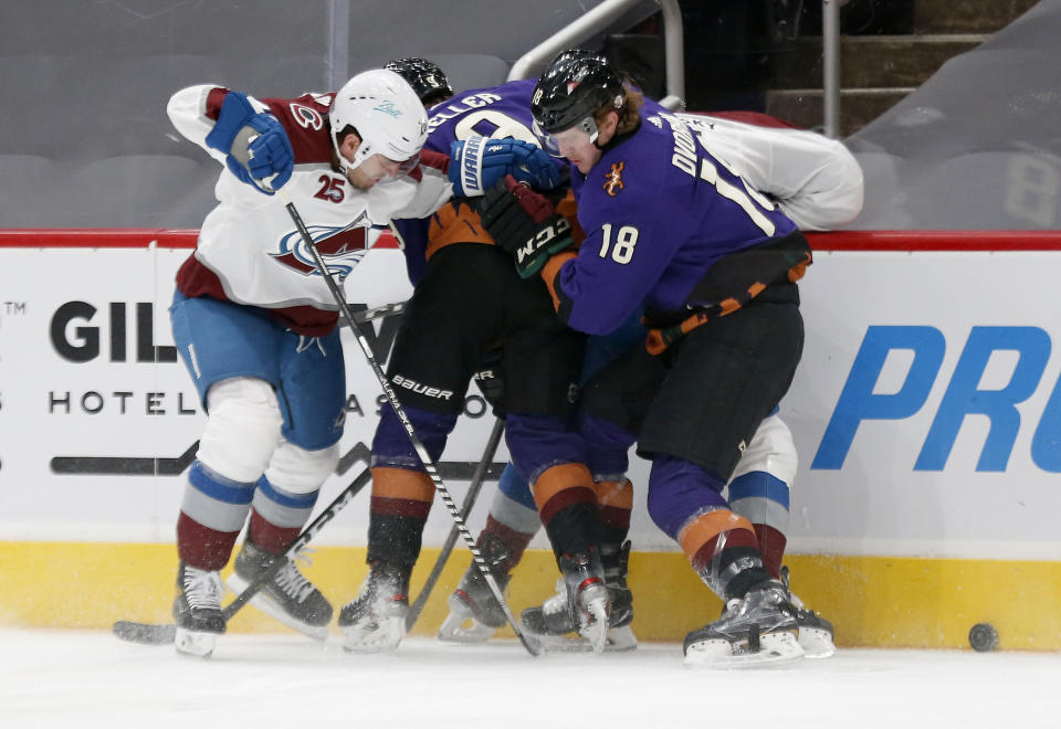 Colorado Avalanche's Logan O'Connor, left, battles with Arizona Coyotes' Clayton Keller, middle, and Christian Dvorak during the first period of an NHL hockey game Saturday, Feb. 27, 2021, in Glendale, Ariz. (AP Photo/Darryl Webb)