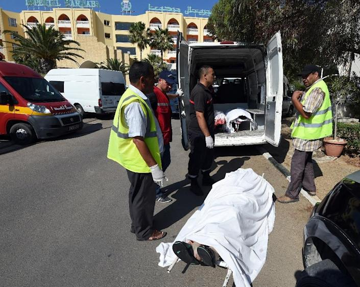Tunisian medics load the bodies of victims into a van after a shooting in the resort town of Sousse on June 26, 2015 (AFP Photo/Fethi Belaid)