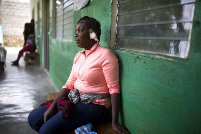 Shelda Similien, who ran out of her before it collapsed when a magnitude 5.9 earthquake hit the night before, waits to be treated at a local hospital in Gros Morne, Haiti, Sunday, Oct. 7, 2018. Similien's five year-old son died when he became buried by the rubble of the collapsed home. (AP Photo/Dieu Nalio Chery)
