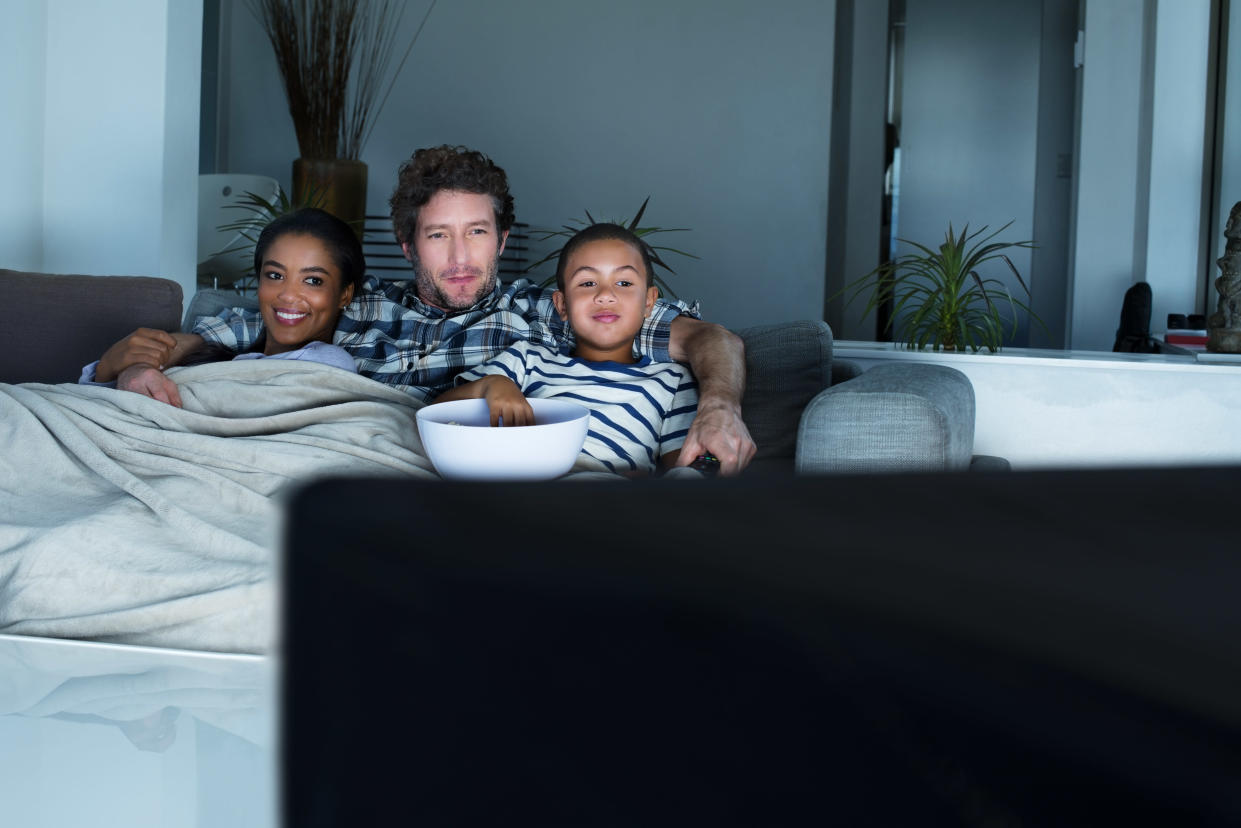 Multi-ethnic family having popcorn while watching TV in living room at home