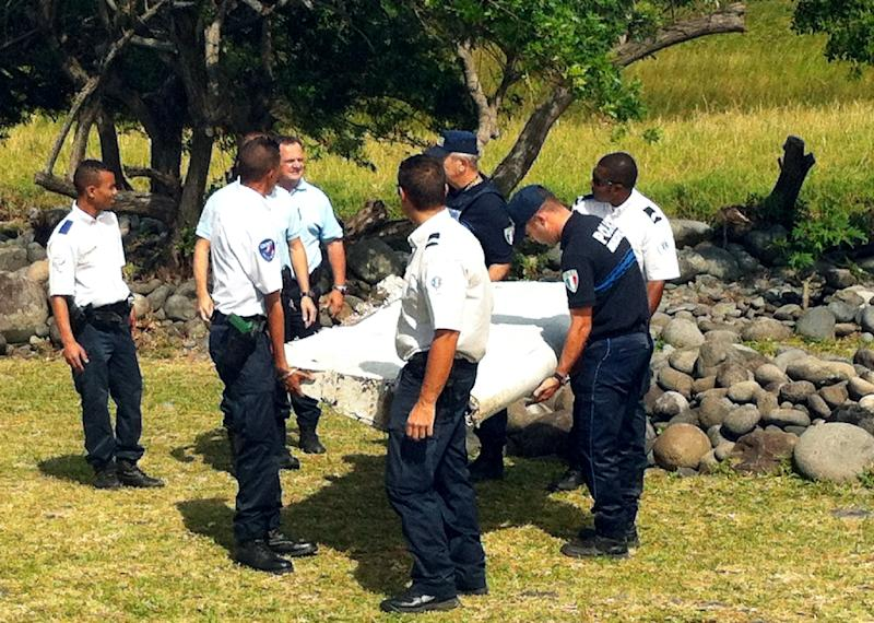Police and gendarmes carry a piece of debris from an unidentified aircraft found in the coastal area of Saint-Andre de la Reunion, in the east of the French Indian Ocean island of La Reunion, on July 29, 2015 (AFP Photo/Yannick Piton)