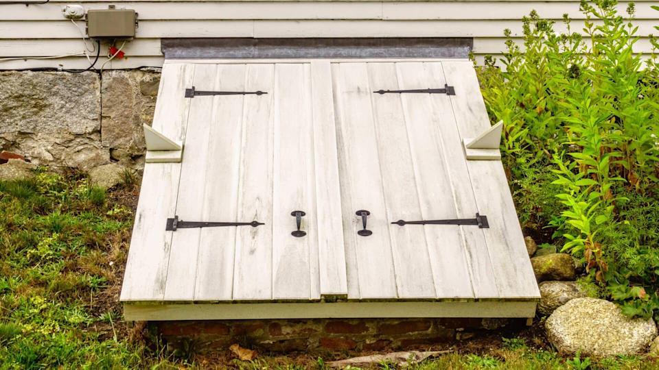 White wooden doors to a storm cellar by stone foundations of an old house in Maine, USA, for themes of stormy weather and safety, readiness, protection - Image.
