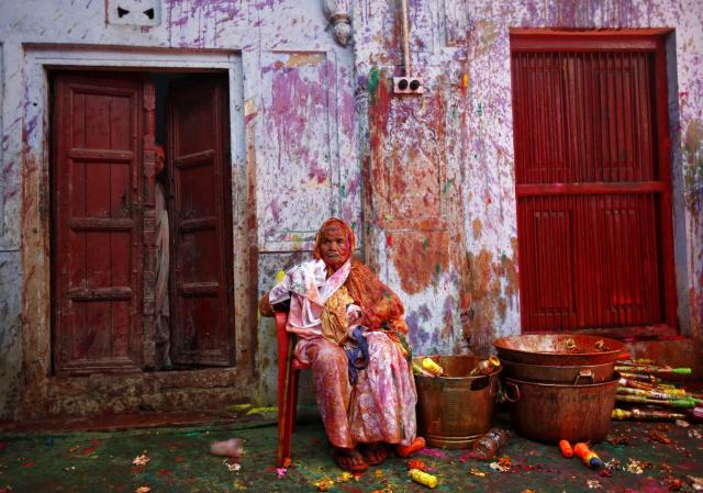 A widow sits on a chair after taking part in Holi celebrations organised by non-governmental organisation Sulabh International at a widows' ashram in Vrindavan in the northern Indian state of Uttar Pradesh March 14, 2014. Traditionally in Hindu culture, widows are expected to renounce earthly pleasure so they do not celebrate Holi. But women at the shelter for widows, who have been abandoned by their families, celebrated the festival by throwing flowers and coloured powder. Holi, also known as the Festival of Colours, heralds the beginning of spring and is celebrated all over India. REUTERS/Ahmad Masood (INDIA - Tags: ANNIVERSARY RELIGION SOCIETY)