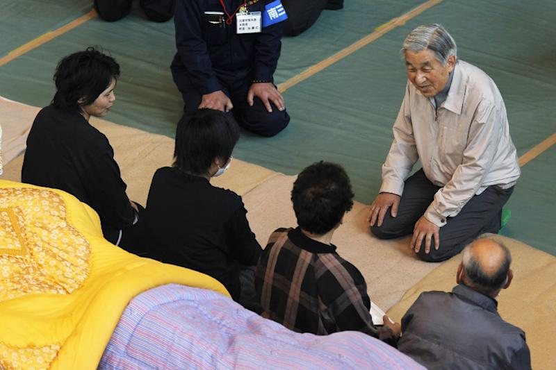 Emperor Akihito and his wife Michiko won plaudits for a popular touch, notably comforting people affected by the 2011 earthquake, tsunami and nuclear meltdown that devastated whole swathes of east Japan and killed thousands (AFP Photo/HIRO KOMAE)