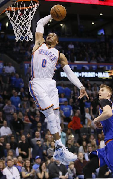 Oklahoma City Thunder guard Russell Westbrook (0) goes up for a dunk in front of New York Knicks forward Kristaps Porzingis (6) during the fourth quarter of an NBA basketball game in Oklahoma City, Wednesday, Feb. 15, 2017. Oklahoma City won 116-105. (AP Photo/Sue Ogrocki)