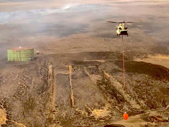 A 25th Combat Aviation Brigade helicopter prepares to drop water on Hawaii wildfires