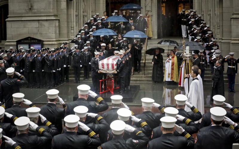 Fire and military officials salute the casket of U.S. Marine Corps Staff Sergeant and FDNY Firefighter Christopher Slutman, as it leaves St. Thomas Episcopal Church, Friday April 26, 2019, in New York. The father of three died April 8 near Bagram Airfield U.S military base in Afghanistan. (AP Photo/Bebeto Matthews)
