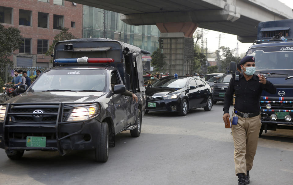 A police officer clears way for a convoy of an anti-terrorism court judge Arshad Hussain Butta arriving at district jail, where the special court setup for the trial of prime suspects in motorway gang-rape case, in Lahore, Pakistan, Saturday, March 20, 2021. A prosecutor says an anti-terrorism court in Pakistan has awarded death penalty and 14 year jail terms to two men held for motorway gang rape of a woman in front of her children last year in eastern Punjab province. (AP Photo/K.M. Chaudary)