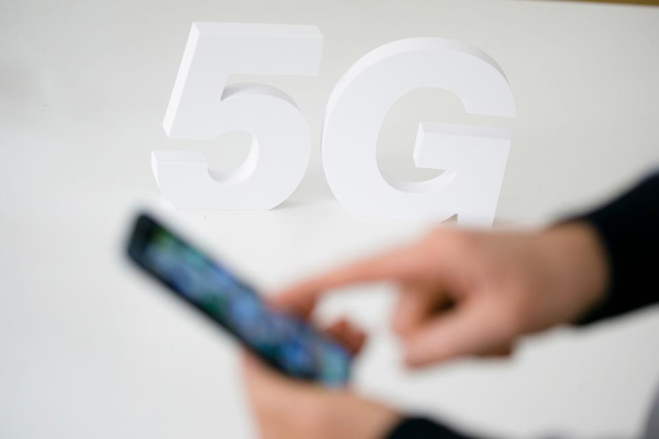 Berlin, Germany - April 12: Symbolic photo on the topic of mobile radio standard 5G. The lettering 5G stand on a table behind a smartphone on April 12, 2019 in Berlin, Germany. (Photo Illustration by Thomas Trutschel/Photothek via Getty Images)