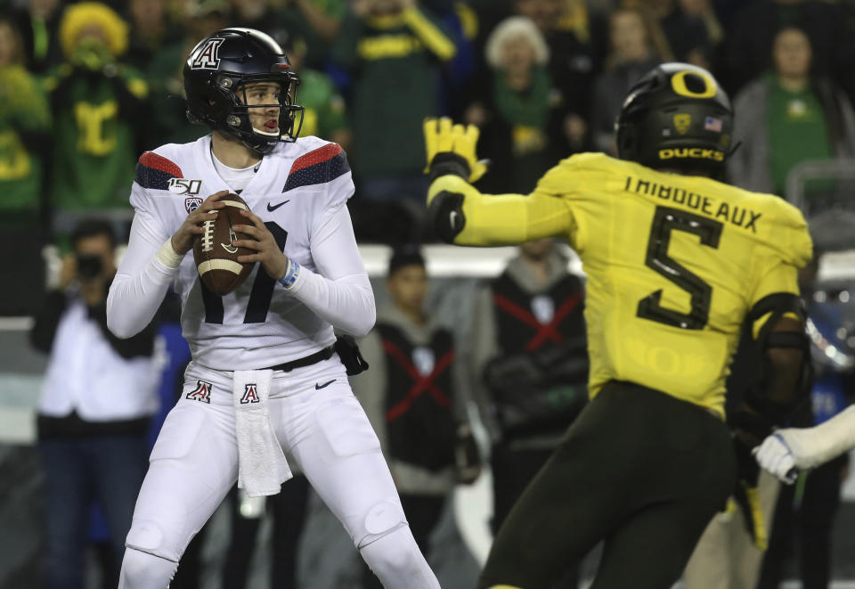 Arizona quarterback Grant Gunnell, left, looks downfield under pressure from Oregon's Kayvon Thibodeaux during the first quarter of an NCAA college football game Saturday, Nov. 16, 2019, in Eugene, Ore. (AP Photo/Chris Pietsch)