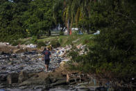 A man walks on the banks of the Guanabara Bay littered with garbage, in Rio de Janeiro, Brazil, Thursday, June 24, 2021. The bay waters where the the 2016 Rio de Janeiro Olympics sailing competitions took place have not been cleaned of sewage, as had been promised. (AP Photo/Bruna Prado)