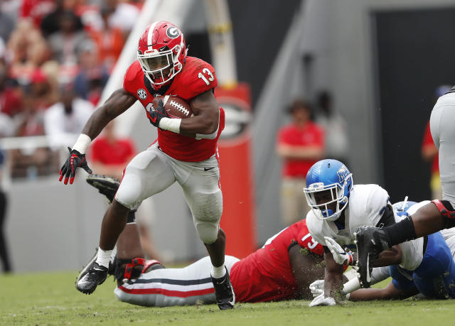 FILE - In this Sept. 15, 2018, file photo, Georgia running back Elijah Holyfield (13) breaks through the Middle Tennessee defense for a big gain in the first half of an NCAA college football game in Athens, Ga. The Bulldogs have produced dynamic running backs over the years, from Herschel Walker to Todd Gurley. The trend continues this season with Holyfield and D'Andre Swift. (AP Photo/John Bazemore, File)