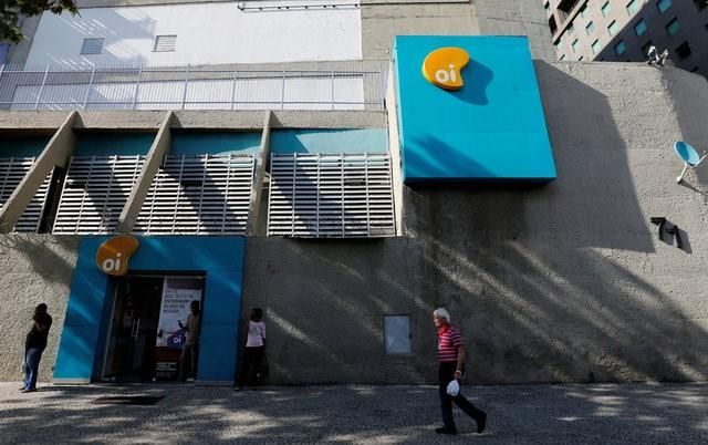 People walk in front of the headquarters of the Brazil's largest fixed-line telecoms group Oi, in Rio de Janeiro